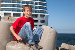 Boy sitting in front of ship Stock Photos