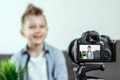 The boy is sitting in front of a SLR camera, close-up. Blogger, blogging, technology, earnings on the Internet. copy space.  stock image