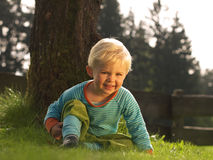 Boy sitting in garden. Boy sitting in the grass and laughing at the camera Royalty Free Stock Photos