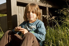 Boy sitting in the garden Stock Photography