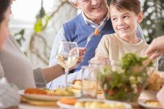 Boy sitting on grandfather`s laps. Boy sitting on his grandfather`s laps during family meal Royalty Free Stock Photos
