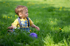 A boy sitting on the grass with a ball Stock Photos