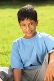 Boy sitting on grass in beautiful bright sunshine Royalty Free Stock Photos