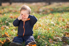 Boy sitting on the grass and hides Royalty Free Stock Photos