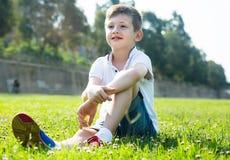 Boy sitting grass Royalty Free Stock Photos