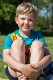 Boy sitting on the grass Royalty Free Stock Image