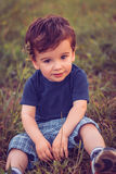 Boy sitting in the grass. And looks at the camera Stock Images