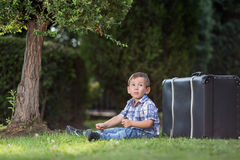 Boy sitting on the grass in the park Stock Image