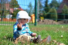 Small boy sitting on the grass at the playground royalty free stock images