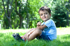 boy, sitting on grass, smelling flower Royalty Free Stock Photos
