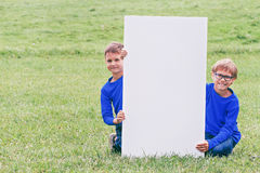 Boy sitting on the grass with vertical blank white placard board outdoors Stock Photo