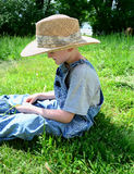 Boy sitting in Grass Stock Photography