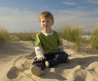 Boy sitting on a grassy dune stock image