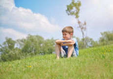 Boy Sitting on Green Nature Hill Outside Royalty Free Stock Images