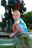 Boy sitting on the gun Royalty Free Stock Photos