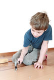 Boy sitting and hammers nail in board Stock Photography