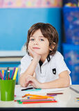 Boy Sitting With Hand On Chin In Drawing Class Stock Images