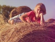 Boy sitting on a haystack Stock Photos