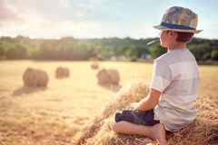 Boy sitting on a haystack in summer watching the sunset stock photos