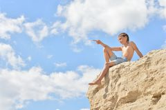 Boy sitting on a hill Stock Images