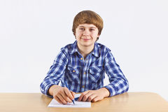 Boy is sitting at his desk and doing his homework Royalty Free Stock Photo