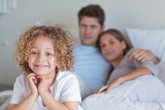 Boy sitting on his parents's bed. While looking at the camera Stock Image