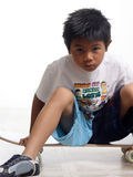 Boy sitting on his skateboard Stock Photos