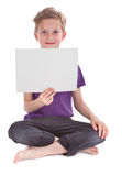 Boy sitting and holding a blank white page Royalty Free Stock Image
