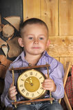 Boy sitting holding clocks in the hands of a waiting midnight Stock Image