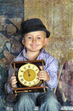 Boy sitting holding clocks in the hands of a waiting midnight Royalty Free Stock Photo