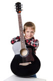 Boy sitting and holding the guitar in vertical position Royalty Free Stock Photography