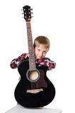 Boy sitting and holding the guitar in vertical position Royalty Free Stock Image