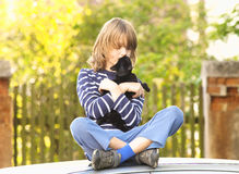 Boy Sitting Holding a Kitten Stock Photo