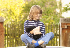 Boy Sitting Holding a Kitten Stock Photography