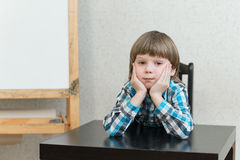 Boy sitting at home and look Royalty Free Stock Photo