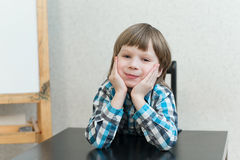 Boy sitting at home and look Stock Image