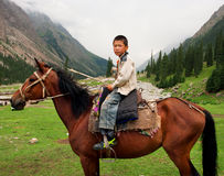 Boy sitting on a horse in a valley between the mountains of Central Asia. BARSKOON, KYRGYZSTAN: Boy sitting on a horse in a valley between the mountains of Royalty Free Stock Photo