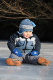 Boy sitting on ice Stock Photos