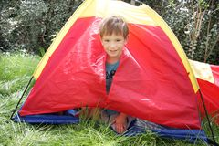Boy sitting inside colorful tent on sunny day Royalty Free Stock Images