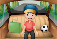 A boy sitting inside a running car Stock Images