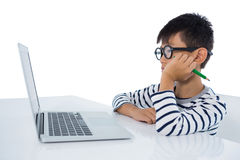 Boy sitting with laptop against white background Royalty Free Stock Photos