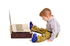 Boy sitting before a laptop Stock Photos