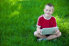 Boy sitting with a laptop on the grass Royalty Free Stock Photography