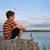 Boy sitting on a large rock watching a seaside landscape Stock Photo