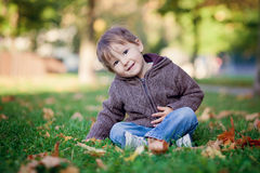Boy, sitting on a lawn, smiling Stock Image