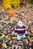 Boy Sitting in Leaves with a Pumpkin Behind Him. A smiling boy sits on a leaf covered ground in a forested landscape with a pumpkin sitting behind him in the Stock Photography