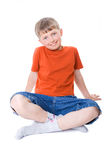 A boy sitting with legs crossed. Isolated on white royalty free stock photography