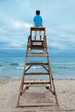 Boy sitting on lifeguard chair royalty free stock photos