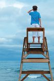 Boy sitting on lifeguard chair stock image
