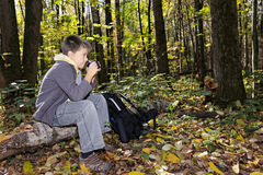 Boy sitting on log with cup sideview Royalty Free Stock Image